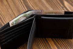 New black leather wallet over dark wooden background. Royalty Free Stock Images