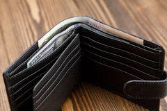 New black leather wallet over dark wooden background. Stock Photo