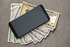 New black modern cellphone on money dollars banknotes background. Modern technology, communication and online trade using gadget. Concept royalty free stock photos