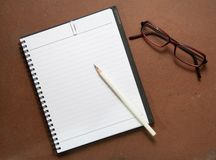 New Black notebook with white pencil and glasses Royalty Free Stock Photos
