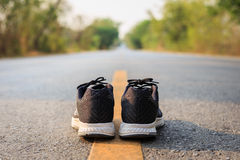 New black running shoes on asphalt road in morning time Royalty Free Stock Photography