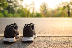 New black running shoes on asphalt road in morning time Stock Photos