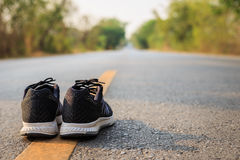New black running shoes on asphalt road in morning time Stock Photography