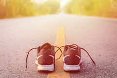 New black running shoes on asphalt road in morning time Stock Images
