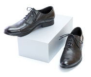New black shoes. New black shoes with laces and grey box on a white background Royalty Free Stock Photos