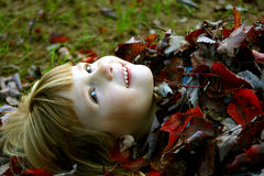 New Blanket. Little girl outdoors covered in leaves Royalty Free Stock Photo