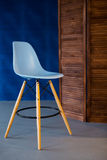 New blue modern chair standing in loft room with blue walls. Royalty Free Stock Images