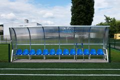 New blue plastic seats on outdoor stadium players bench, chairs with new paint below transparent plastic roof. Stock Images