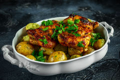 New boiled potatoes with dill and butter served with baked skinless boneless chicken thighs in vintage casserole.  stock photo