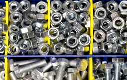 New bolts and nuts sorted in a container with yellow, blue partitions closeup flatlay, background, mechanic work concept stock photos