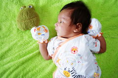 New Born Baby. A new born baby looking at a frog doll Royalty Free Stock Images