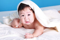 New Born Baby. Portrait of a little new born baby boy climbing on bed Royalty Free Stock Image