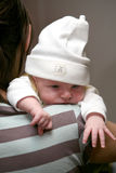 New-born baby. A new born baby wearing a cap lying over her mother's shoulder Royalty Free Stock Image