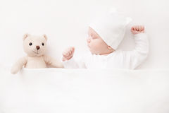 New born Baby girl sleeping with her teddy bear Stock Image