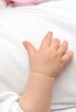 New born baby hand. On white fabric background Stock Photo
