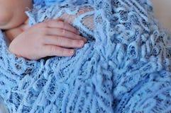 New born baby hand. On blue blancet stock photo