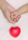 New born baby hand in mom palm with red heart Royalty Free Stock Images
