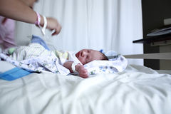 New born baby with mother. Selective focusing on a new born baby on the hospital bed Royalty Free Stock Photos