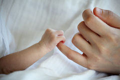 New Born Baby's Hand Gripping Mother Finger Stock Photo