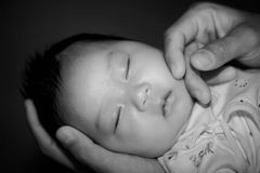 New Born Baby Sleep. Ing in the hands of his father,white and black Royalty Free Stock Photography