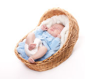 New born baby sleeps in basket Stock Photo