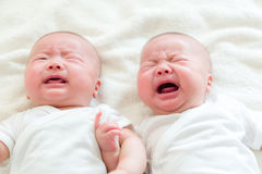 New born baby twins cry. Lying on bed Stock Photo