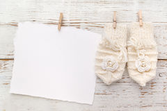 New Born or baptism Greeting Card. Blank with baby girl gloves on white wooden background Royalty Free Stock Images