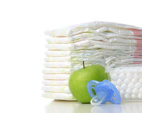 New born child care stack of diapers pacifier and big cotton ear Stock Photos