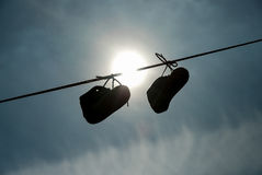 New-born child shoes hanging on the lace with clear sky and sun. In background Royalty Free Stock Image