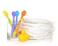 New born child stack of diapers baby little spoons in glass and Stock Photos