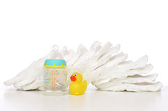 New born child stack of diapers nipple soother baby feeding. Milk bottle with water and yellow duck on a white background stock images