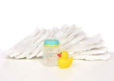 New born child stack of diapers nipple soother baby feeding milk. Bottle with water and yellow duck on a white background royalty free stock photography