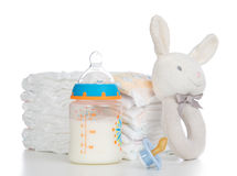 New born child stack of diapers, nipple soother, beanbag bunny. Toy and baby feeding bottle with milk on a white background stock photo