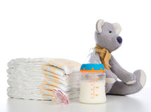 New born child stack of diapers, nipple soother, teddy bear toy. And baby feeding bottle with milk on a white background royalty free stock image