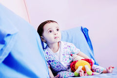 Baby girl. Arabian egyptian newborn baby girl sitting on bed and staring Royalty Free Stock Photos