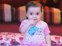 Baby girl smile. Arabian egyptian newborn girl puts finger in her mouse and smiles Royalty Free Stock Image