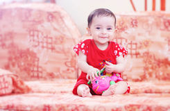 Smiling baby girl. Smiling arabian egyptian newborn baby girl sitting on bench and playing Royalty Free Stock Photo