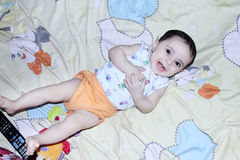 Smiling baby girl. New born baby girl sitting on bed and laughing Royalty Free Stock Photos