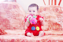 Smiling baby girl. Arabian egyptian newborn baby girl playing with her toy and smiling Royalty Free Stock Image