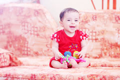 Laughing baby girl. Arabian egyptian newborn baby girl playing with her toy and laughing Royalty Free Stock Image