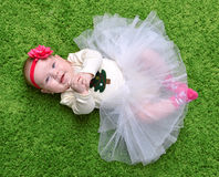New born Infant child baby girl lying happy smiling on green gra Royalty Free Stock Photo