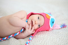 New borng baby dressed in color hat. Smiling new borng baby dressed in owl-stiled hat Royalty Free Stock Photography