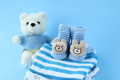 New boy clothes. Stack of  clothes  for baby boy on blue background Stock Photos