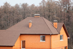 New brick house with modular chimney, Stone Coated Metal Roof Tile, plastic windows and rain gutter. Stock Image