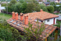 New brick house with red roof tile pattern and modular chimney, plastic windows and rain gutter stock photography