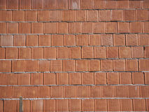 New brick wall built of red bricks on mortar. Background for construction work. Stock Photos