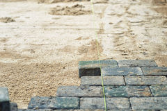 New bricks being laid as paving on earth Royalty Free Stock Photos