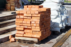 New bricks are stacked on a pallet and bags near the trade pavilion. Stock Photos