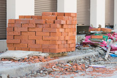 New bricks are stacked on a pallet stand at trade pavilions around construction debris Royalty Free Stock Image