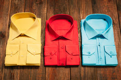 New bright men's shirts on a wooden background Royalty Free Stock Images